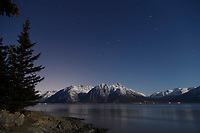 winter landscape of moonlight on shoreline of Turnagain Arm with Chugach Mountains  and stars above Turnagain Arm with Seward highway at base.  Stars and north star