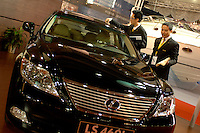 A man cleans a Lexus car in the Guanzhou Luxury Goods Fair in China.