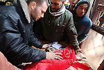Palestinians mourn next to the body of Ishaq Hassan, 28, who was shot dead by Egyptian border guards as he crossed from the Gaza Strip into Egypt, during his funeral in Gaza city on December 31, 2015. Ishaq Hassan, who was said to suffer from mental illness, was shot dead after he crossed naked the posts and fencing marking the border between the Palestinian enclave and Egypt. Photo by Mohammed Asad