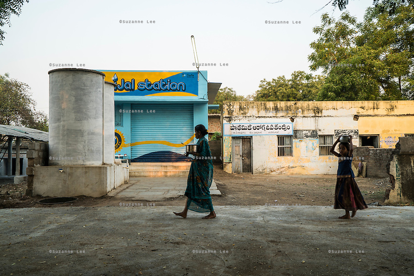 Villagers walk past the iJal water station in Peddapur, a remote village in Warangal, Telangana, India, on 22nd March 2015. Safe Water Network works with local communities that live beyond the water pipeline to establish sustainable and reliable water treatment stations within their villages to provide potable and safe water to the communities at a nominal cost. Photo by Suzanne Lee/Panos Pictures for Safe Water Network