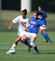 Gloria Douglas (7) of Virginia has the ball tackled away from her by Cassie Pecht (11) of Duke during the game at Klockner Stadium in Charlottesville, VA.  Virginia defeated Duke, 1-0.