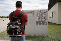 Germany. Bayern state. The Dachau Concentration Camp Memorial Site. A tourist with a backpack reads the informations on the roll-call area where the prisoners were counted every morning and evening and assigned to their work details. Punishment measures were announced and carried out here publicly to intimidate the prisoners. The more the number of prisoners increased the longer and more exhausting the roll-call procedure became. Dead prisoners had to be brought to roll call and included in the count. On march 22, 1933, the first concentration camp was opened in Dachau by the Nazis. It became a model for all later concentration camps established under the control of the SS men and the Third  Reich. © 2007 Didier Ruef