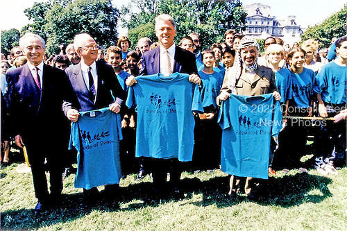 "Israeli Foreign Minister Shimon Peres, left, Israeli Prime Minister Yitzhak Rabin, left center, United States President Bill Clinton, center, and Palestine Liberation Organization Chairman Yasser Arafat, right, pose holding t-shirts of ""Seeds of Peace"" after they signed the Oslo 1 Accords on the South Lawn of theWhite House on September 13, 1993.  The 47 ""Seeds of Peace"" boys came from Israel, Egypt, and the Palestinian Territories and were the honored guests for the signing ceremony.  John Wallach, President and Founder of ""Seeds of Peace"" can be seen to the immediate left behind Prime Minister Rabin. .Mandatory Credit: Bob McNeely - White House via CNP"