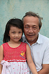 "Trinh Cong Tan, 66, a former South Vietnamese army intelligence officer, poses for a portrait with his six-year-old daughter in Nha Trang, Vietnam. Trinh spent six years in a reeducation camp after the war, where ""they made me pull a plow like a water buffalo,"" he said. Later, ""when I got out, I had one shirt, one pair of pants and nothing else. I wanted to kill myself. But my mother told me I could not die yet. 'You still have your hands and your strength and you can start over again,' she said.'"" Today, he runs a small roadside cafe on the outskirts of the city. July 13, 2011."