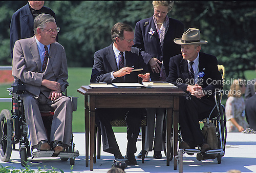 United States President George H. W. Bush hands a ceremonial pen to Justin Dart after he signed the Americans with Disabilities Act of 1990 into law during a ceremony on the South Lawn of the White House in Washington, D.C. on July 26, 1990. Pictured (left to right): Evan J. Kemp, Jr., Chairman, U.S. Equal Employment Opportunity Commission; President Bush; Sandra Parrino; and Justin Dart.  The act prohibited employer discrimination on the basis of disability. <br /> Credit: Ron Sachs / CNP