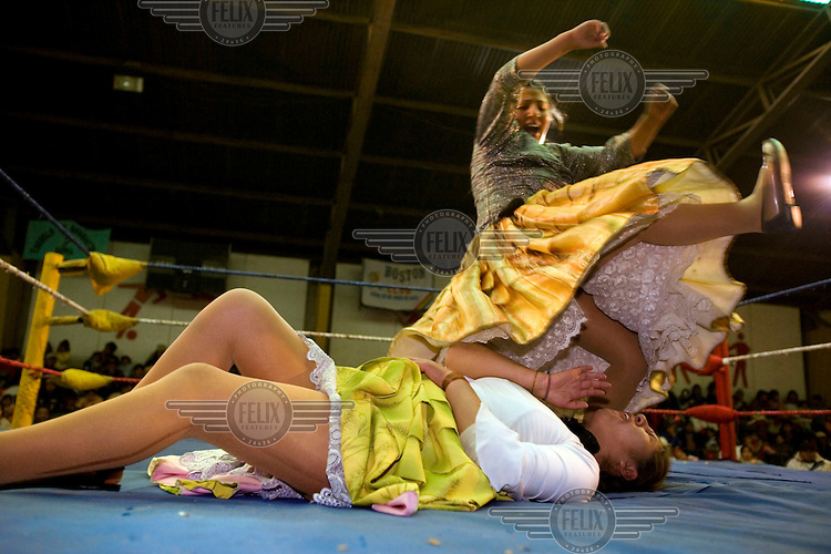 26 year old wrestler Juanita la Carinosa (fighting name), Mery Llanos Saenz (real name) jumps on 17 year old Alicia Flores (fighting name), Patricia Kaly (real name) during a fight at the Multifuncional building in El Alto. Patricia and Mery are Cholitas, wrestlers of native Aymara descent. When Cholitas fight they wear traditional costume.