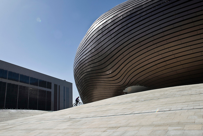 A boy rides his bike near the newly constructed Ordos Museum, which was designed by Chinese architect Ma Yansong.