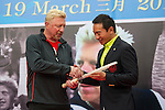 Tennis legend Boris Becker (left) offers the tennis racket he won the Wimbledon tournament in 1985 with to Mission Hills Vice Chairman Tenniel Chu (right) during the press conference for the opening of Boris Becker Tennis Academy at Mission Hills Resort on 19 March 2016, in Shenzhen, China. Photo by Lucas Schifres / Power Sport Images