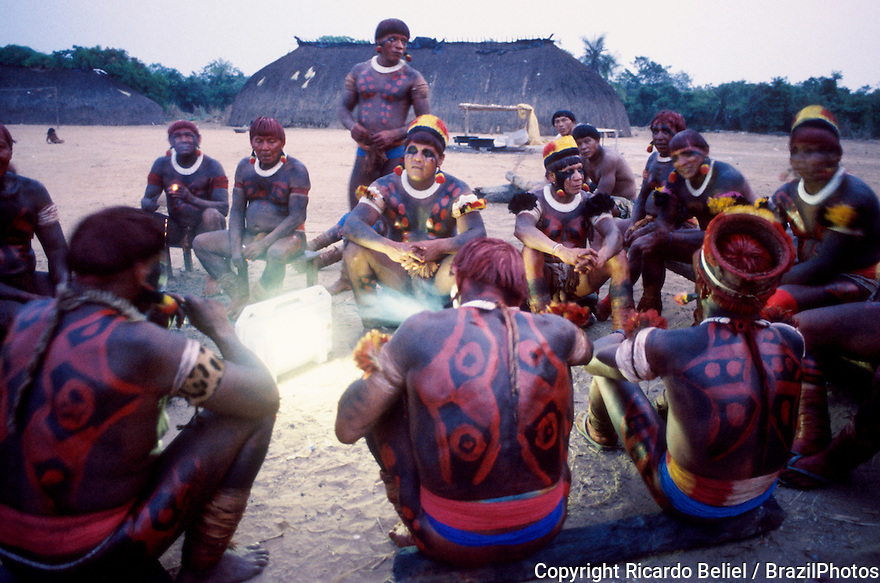 Body-painted indigenous men gather around a solar powered electric torch, Xingu National park, Amazon rainforest, Brazil.