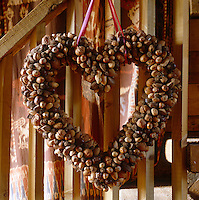 A heart-shaped wreath made of nuts hangs on the staircase
