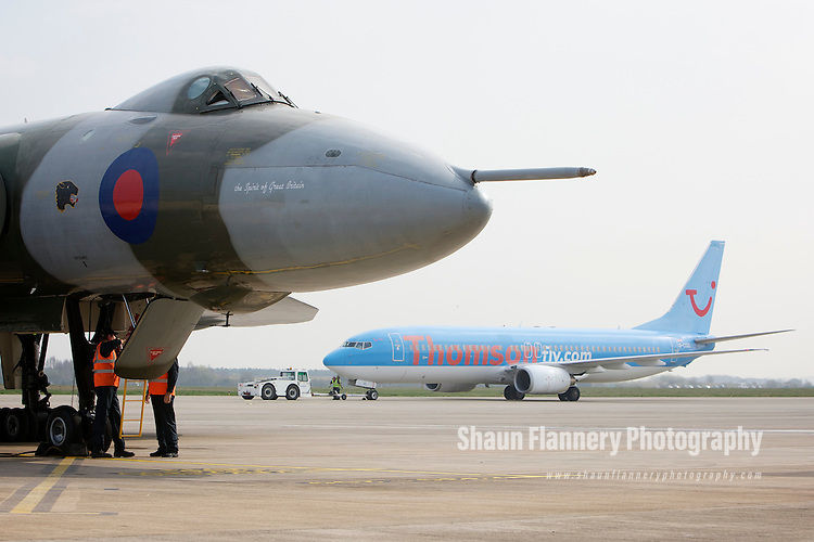 Pix: Shaun Flannery/shaunflanneryphotography.com...COPYRIGHT PICTURE>>SHAUN FLANNERY>01302-570814>>07778315553>>..29th March 2011..............The last flying Vulcan, XH558,  touches down at Robin Hood Airport Doncaster Sheffield. .Vulcan XH558 is to spend the summer based at the airfield where she once stood on Quick Reaction Alert during the Cold War..A Thomsonfly Boeing 737 pictured in 'the shadow' of the Vulcan..
