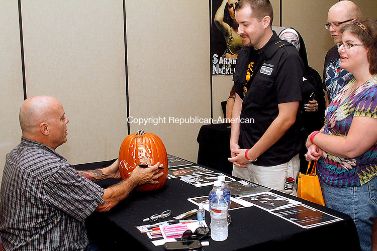 WATERBURY, CT.- 23 AUGUST 2014 - 082314JW02 - Tony Moran who played Michael Myers in John Carpenters movie Halloween, signs a pumkin with the characters likeness for Ryan Wickstrand and Kristin Lukas during the Connecticut Horrorfest at the Courtyard by Mariott Saturday afternoon.<br /> Jonathan Wilcox Republican-American