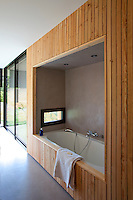 The ensuite bathroom is built into a wood-clad alcove in the master bedroom
