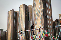 A man balances on a swing during Nauryz celebrations, the traditional new year holiday. Behind him rise a group of modern high rise buildings.
