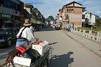 Woman cycling along the streets of downtown Yangshuo, Guangxi, China.