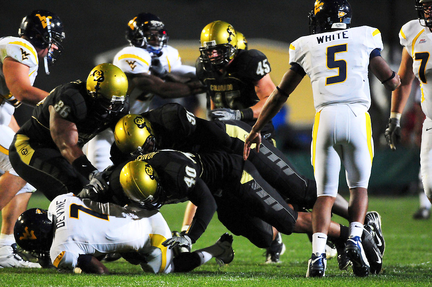 18 September 08: Colorado defensemen, linebacker Brad Jones (40), defensive end Maurice Lucas (91), defensive tackle George Hypolite (86) and linebacker Jeff Smart (45) ensure that a handoff rushing play from West Virginia quarterback Pat White (5) to runningback Noel Devine (7) goes nowhere. The Colorado Buffaloes defeated the West Virginia Mountaineers 17-14 in overtime at Folsom Field in Boulder, Colorado. For Editorial Use Only.