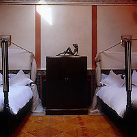 A pair of four-poster beds flank an Art Deco cupboard on which stands a 1920s sculpture of a reclining woman