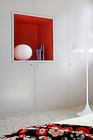 A brightly painted recessed shelf in the wall to wall cupboards becomes a feature of the bedroom