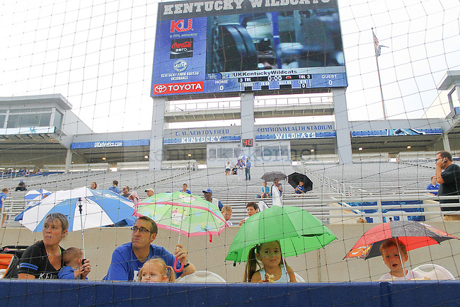 A family sheilds themselves from the rain prior to the open practice during Fan Day on Friday, August, 9th, 2013 at Commonwealth Stadium in Lexington, KY. Photo by Michael Reaves | Staff