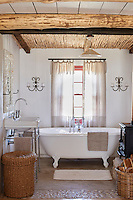 A white country bathroom with a beamed ceiling. A free-standing roll top bath with claw feet stands in front of a window. A wicker laundry basket is placed beside a washbasin with stainless steel stand.
