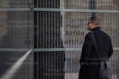 Man stands in front of a wall bearing the names of victims at Budapest's Holocaust Memorial Centre, Hungary on January 27, 2013. ATTILA VOLGYI