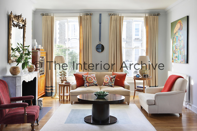 Floor-to-ceiling curtains emphasise the height of the living room whilst tying in with the cream of one of the sofas and the patina of the wood flooring