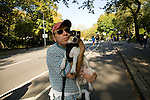 Man with hat hugging his pet terrier dog in Central Park, NYC