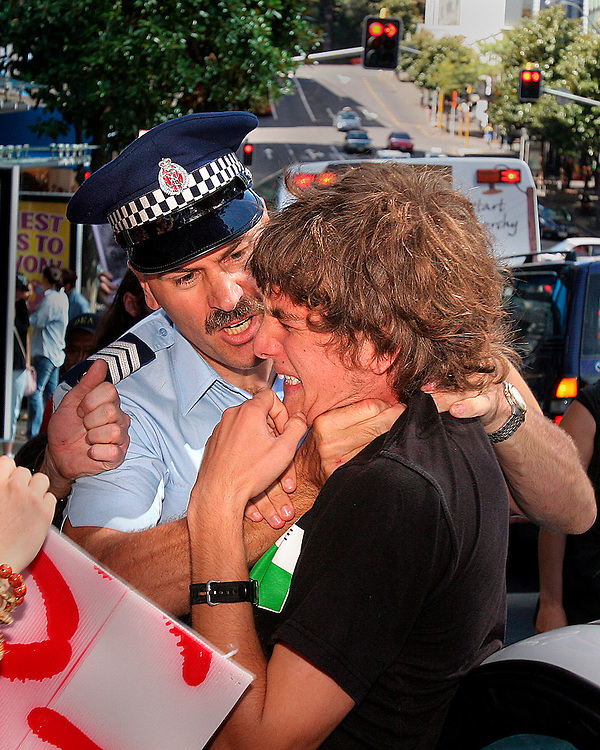 A protester is threatened with arrest while being restrained in an unconventional manner during an anti-Iraq war demonstration in Auckland.  19Mar05.  Photo © James Madelin
