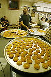 A Palestinian sweet maker bakes a cakes at a shop in the old city of Jerusalem on July 31, 2009.  Photo by Mahfouz Abu Turk
