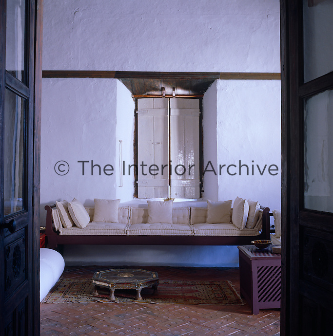 Looking through a pair of double doors into the whitewashed living room with a long sofa placed underneath a window with closed wooden shutters