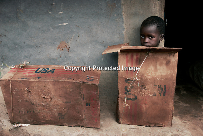 UMYAMA, UGANDA MAY 21: A boy sits in a cardboard box outside a hut on May 21, 2005 in Umyama, a camp for displayed people in northern Uganda. About 1.5 million people have fled villages and live in about 180 squalid Internally Displaced People (IDP) camps, which has changed the rural life in Northern Uganda. Many children in this area are afraid of being abducted by the Lord's Resistance Army (LRA). The rebel group has brought terror to Northern Uganda for almost twenty years, fighting the Ugandan government. The victims are usually children, which are abducted and used as child soldiers and sex slaves. (Photo: Per-Anders Pettersson)..