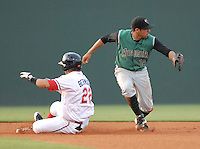 Ronald Bermudez (22) of the Greenville Drive slides into second with a double as shortstop Juan Martinez (14) waits for the throw during Spartanburg Night with the Greenville Drive on June 8, 2010, at Fluor Field at the West End in Greenville, S.C. Photo by: Tom Priddy/Four Seam Images
