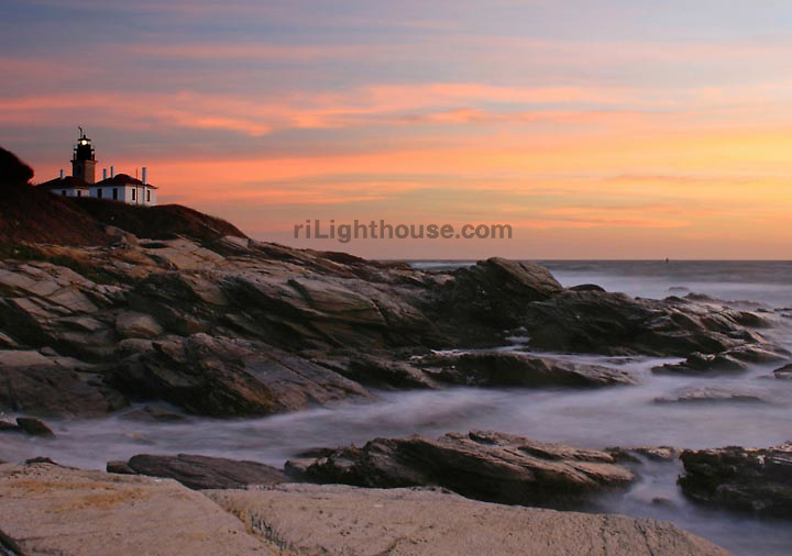 The setting sun lights the sky on fire as waves roll ashore by Beavertail Lighthouse.