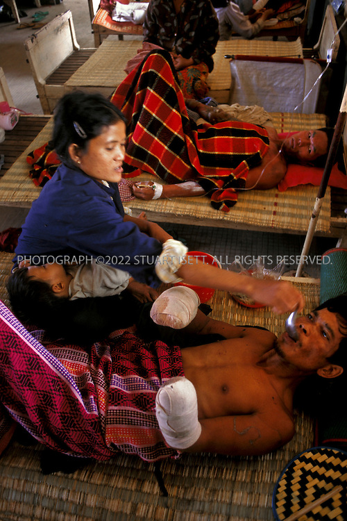Battambang, Cambodia..Landmine victims recovering at Battambang Hospital. her a wife spoon feeds her husband, a farmer who lost both his hands attempting to clear landmines himself...©2003 Stuart Isett All rights reserved
