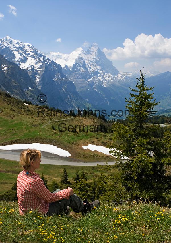 CHE, Schweiz, Kanton Bern, Berner Oberland, Grindelwald: Grosse Scheidegg - Blick auf die Gipfel von Eiger (3.970 m) mit Eigernordwand und Moench (4.107 m) - Frau sitzt in Blumenwiese | CHE, Switzerland, Canton Bern, Bernese Oberland, Grindelwald: Grosse Scheidegg - view at peaks of Eiger (3.970 m) with Eiger-Northface and Moench (4.107 m) - woman sitting in flower meadow