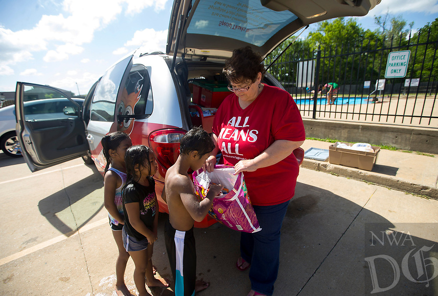 NWA Democrat-Gazette/JASON IVESTER<br /> Pam Sweeney with the Sonora Elementary Mobile Library hands out snacks Tuesday, June 13, 2017, to children at the pool at the Montecito Springs Apartment complex in Springdale during one of the library's stops.