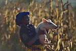 A woman carries a pig in Kaluhoro, Malawi. With support from the Ekwendeni Hospital AIDS Program, she and other villagers participate in a Building Sustainable Livelihoods program, working together to earn and save money, raise more nutritious food, and receive vocational training.