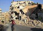 A Syrian boy rides a bicycle past the rubble of buildings which destroyed by forces of Syria's President Bashar al-Assad, in a rebel-controlled area in the northern Syrian city of Aleppo, on August 31, 2015. Photo by Ameer al-Halbi