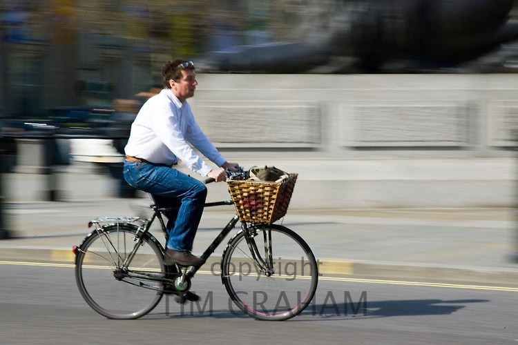 Cyclist riding a bicycle in Trafalgar Square, London, England, United Kingdom