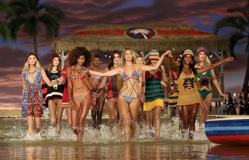 Models splash through a water feature on the set during the Tommy Hilfiger presentation during New York Fashion Week in New York, Monday, September 14, 2015. AFP PHOTO/TREVOR COLLENS