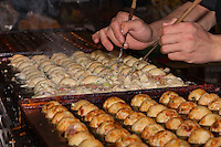 Chef Ryota Akai of Japan forms takoyaki during a demonstration of takoyaki cooking at Mitsuwa Market in Costa Mesa, California.  To form the takoyaki the batter is first cooked somewhat on the pan, and then the half-cooked batter is delicately (and quickly) rolled into a ball using chopsticks.  Compare all the images of this sequence to see the process; the last 7 of these frames were shot over only two seconds.