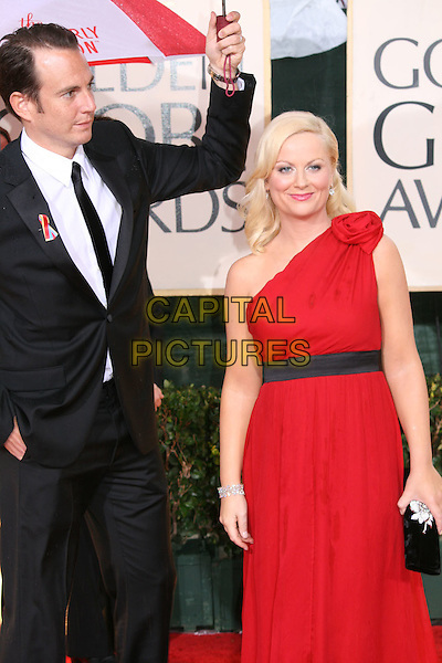 WILL ARNETT & AMY POEHLER .Arrivals at the 67th Golden Globe Awards, he Beverly Hilton Hotel, Beverly Hills, California, USA, .January 17th, 2010..globes half length red one shoulder dress black waistband gown black suit tie married couple husband wife umbrella raining diamond bracelet clutch bag 3/4  .CAP/AW/MAZ .©Maz/Weber/Capital Pictures.