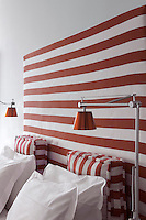 Red and white striped squab cushions match the tall  upholstered headboard in this guest bedroom