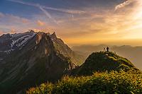 Photographer on grassy ridge at sunset with Säntis peak in the background, Wasserauen, Appenzell, Switzerland, Europe