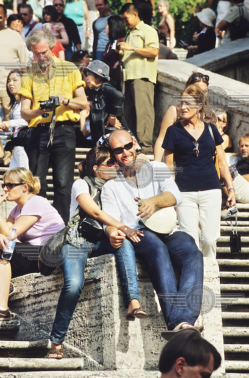 Couple sitting on the Spanish Steps. .