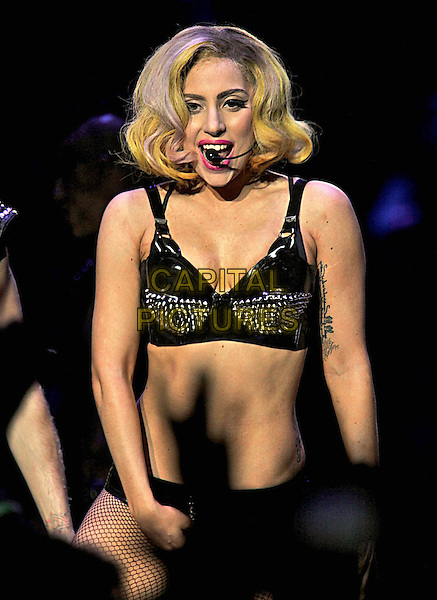 LADY GAGA (Stefani Joanne Angelina Germanotta) .performs live during Monster Ball 2010 North American Tour at the Pepsi Center in Denver, Colorado, USA,.July 28th 2010..music concert gig on stage half length black conical cone bra top pvc silver studded studs knickers microphone singing tattoo midriff                                                                    .CAP/RKE/RT.©Rod Tanaka / RockinExposures/Capital Pictures.