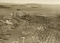 historical aerial photograph of Oakland, Alameda, Port of Oakland with Bay Bridge and Golden Gate Bridge under construction, California, 1935