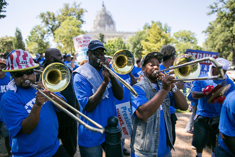 UNITED STATES - JULY 22: Men play trombones to pump up the crowd during a rally on Capitol Hill in Washington, Wednesday, July 22, 2015, to push for a raise to the minimum wage to $15 an hour. (Photo By Al Drago/CQ Roll Call)