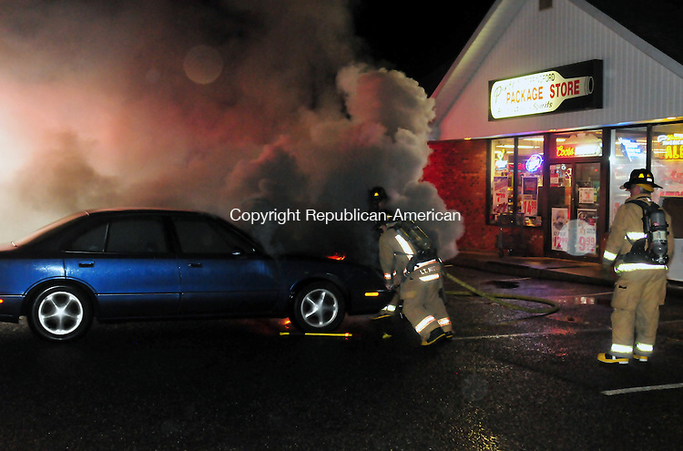 THOMASTON, CT, 16 NOV 11-111611AJ01- A trip to Ponte's Torringford Package store on Wednesday evening turned out to be an adventure for Nick Beverly of Torrington. Beverly, when he returned to his 1997 Oldsmobile, found his car on fire. The light blue car was spewing a pungent plastic smelling smoke from beneath the hood. Beverley said that he ran back into the store to find a fire extinguisher and returned with water in an attempt to quell the growing flames. In the meantime a passerby pushed the car into the middle of the parking lot, which was where firefighters found the car with flames illuminating the undercarriage. Firefighters used a fire hose attached to a tanker to flood the flames while raising the hood only enough to spray water on the engine. The fire was under control and the hoses were rolled up about 10 minutes after the 8:16 p.m. call. The cause of the blaze was unknown Wednesday night. Alec Johnson / Republican-American