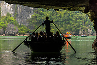 Rowing tourists through a cave at Halong Bay, North Vietnam. The bay features 3,000  limestone and dolomite karsts and islets in various shapes and sizes sprinkled over 1,500 square kilometers. It offers a wonderland of karst topography. It is a UNESCO World Heritage Site.